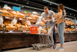 Full length portrait of happy young family shopping for groceries in supermarket together with little boy, while choosing fresh bread loaf in bakery department - 181369862