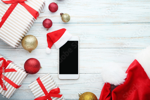 Smartphone with red santa hat and christmas baubles on wooden table