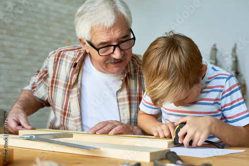 Portrait of old man teaching cute little boy woodwork, making wooden models toge Poster