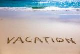 Vacation text on sandy beach