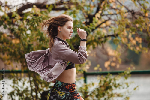 Staande foto Jogging Young sporty girl jogging in city park at autumn day.