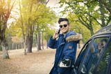 young adult with car and outdoor mobile phone - 181386081