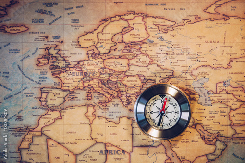 Fototapeta Old compass on vintage map. Adventure stories background. Retro style. The map used for background is in Public domain.