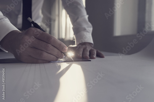 Fototapeta Retro style image of an architect working at a table in an office backlit by a bright sunlight