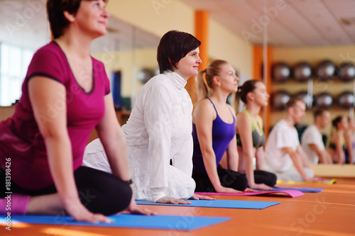 Poster adult woman 40s engaged in yoga in the fitness center