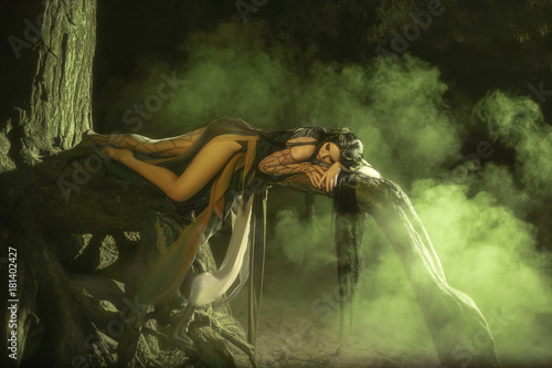 A fabulous, forest nymph with long hair lies and sleeps on a tree branch. Background dark night and fog. Mythical character of Gian