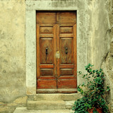 Old weathered wooden door of village house, Tuscany, Italy.
