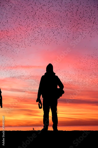 Foto op Canvas Koraal A silhouetted man standing on a black pier at sunset with hundreds of starling bird in the red and orange sky above them, the sunset is deep orange and pink