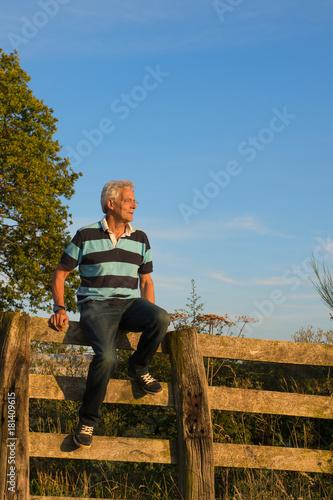 Poster Senior man on fence