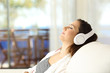 Woman relaxing listening to music on a couch