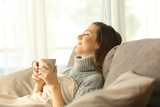 Woman relaxing at home holding a coffee mug - 181410851