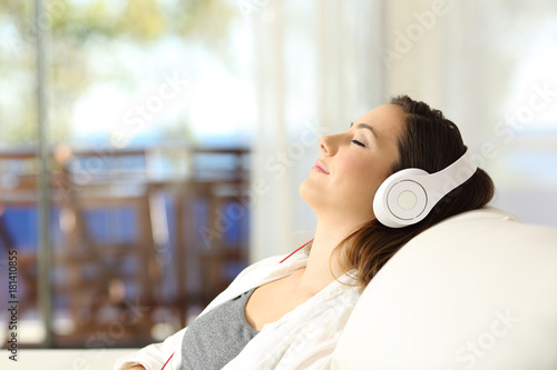 Fotobehang Muziek Woman relaxing listening to music on a couch