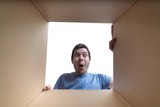 Young surprised man is looking inside cardboard box. - 181411899