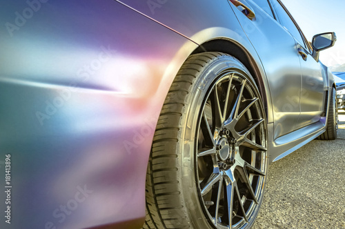 Matte paint on the side of a car with black rims - 181413896