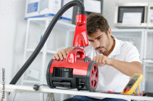 handsome young repairman fixing vacuum cleaner Plakát