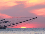 A Thai shrimp boat is silhouetted on the sunset ocean, Ko Kut, Thailand
