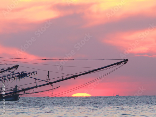 Foto op Aluminium Zee zonsondergang A Thai shrimp boat is silhouetted on the sunset ocean, Ko Kut, Thailand