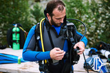 Male diver in wetsuit checking equipments before immerse - 181439213