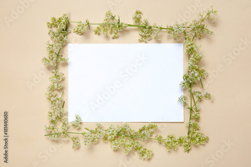 Poster A floral frame in a circle of a white sheet of paper lies on a beige background