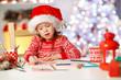child girl writing letter santa home near Christmas tree