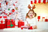 child girl writing letter santa home near Christmas tree. - 181441855