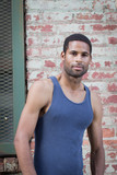Portrait of young handsome African American man in tank top against brick wall - 181449083