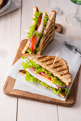 Sandwiches with ham, cheese, tomatoes and a salad with toasted bread.