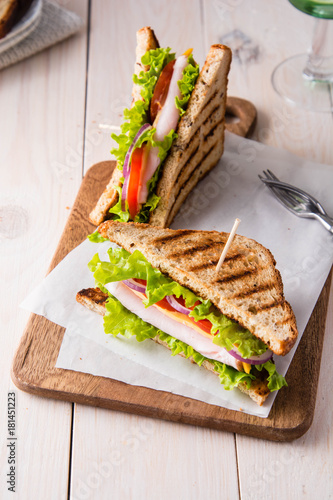 Sandwiches with ham, cheese, tomatoes and a salad with toasted bread. - 181451223