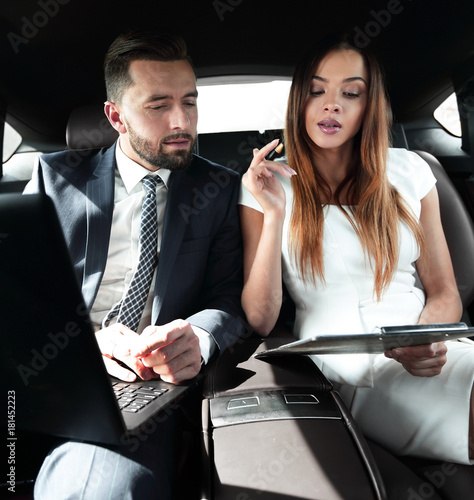 man and woman discussing work documents in taxi
