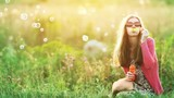 Young woman in meadow blowing soap bubbles  - 181464079