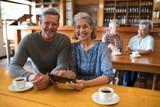 Smiling senior couple using digital tablet in restaurant - 181464475
