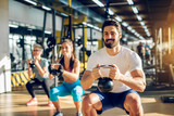 Fototapety Attractive handsome bearded man holding kettlebell and doing squats in a fitness group with two girls in the modern gym.