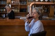 Senior woman having glass of red wine at counter