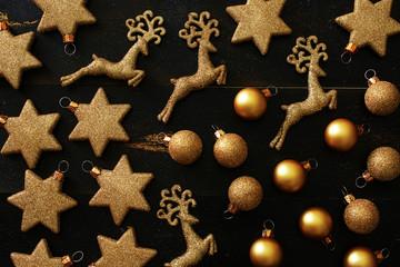 Top view of golden Christmas decorations (balls, stars, deers) over black background