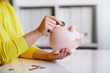 Close up of woman putting coin into piggy bank