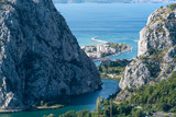 View to Omis from the mountains with the river Cetina, the town, the adriatic sea and in the background the island of Brac with a clear blue sky. - 181477828