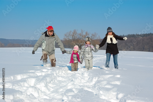 Happy family walks in winter, having fun and playing with snow outdoors on holiday weekend