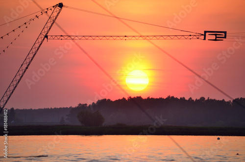 Foto op Plexiglas Oranje eclat sunset on the river and wakeboard cableways
