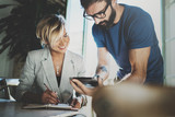 Coworkers working process at home.Young blonde woman working together with bearded colleague man at modern home office.People using electronic devices.Blurred background.Horizontal.