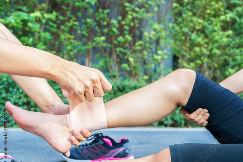 Woman runner ankle being applied bandage by man in park. injury ankle