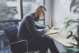 Skilled designer caucasian man drawing abstract sketch with pen.Art work process.Creative hobby.Noting ideas in copy book on workspace desk with papers in modern studio with panoramic windows.Blurred. - 181498878
