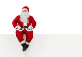 Santa Claus sitting at the edge of a banner isolated on white background with copy space