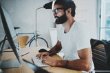 Bearded professional architect wearing eye glasses and white tshirt working at modern loft studio-office with desktop computer.Blurred background. Horizontal.