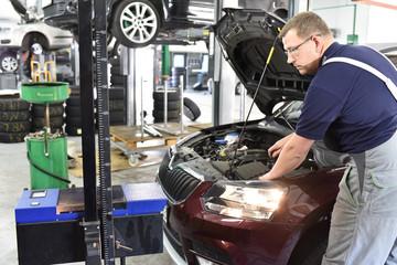 KFZ Mechaniker stellt Licht am Autoscheinwerfer in einer Werkstatt ein // car mechanic adjusts headlight in a garage