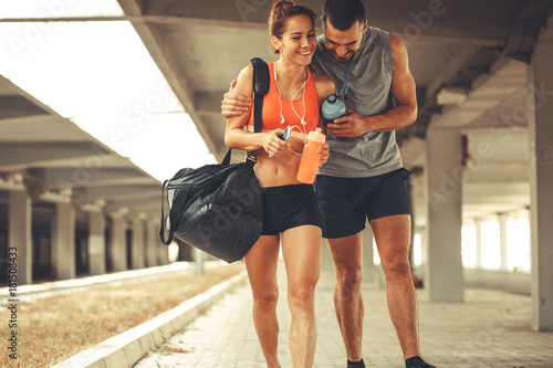 Sticker Young couple walking on street in sports wear.They going to gym.