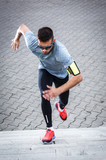 Young man doing workout at the street.He running up the stairs. - 181508802