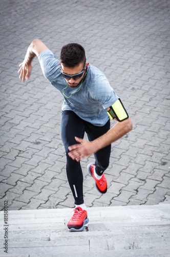 Fototapeta Young man doing workout at the street.He running up the stairs.