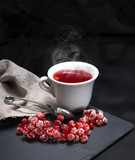 hot tea from red viburnum in a white ceramic cup - 181511035