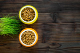 Dry pet food in bowls and green grass in pot on dark wooden background top view copyspace - 181511042