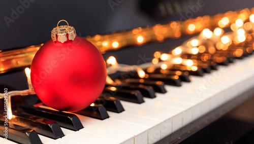 Christmas ball and lights on a piano keyboard